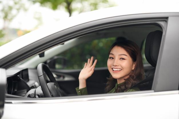 Witaj! piękna młoda wesoła kobieta patrząca na kamerę z uśmiechem i machającą siedząc w swoim samochodzie
