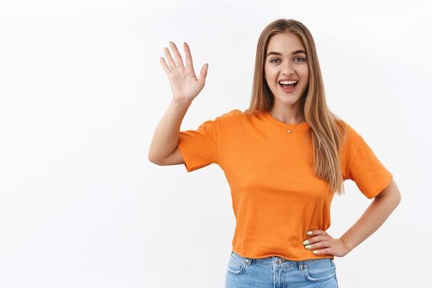 Witaj sąsiedzie. uśmiechnięta blond dziewczyna stojąca przy oknie w domu podczas kwarantanny i machająca do przyjaciółki po drugiej stronie ulicy, żeby się przywitać