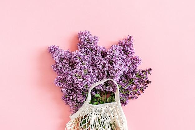 Witaj wiosno. bukiet kwitnącego bzu w ekologicznej siatkowej torbie wielokrotnego użytku na różowym tle. koncepcja bez plastiku, zero strat.