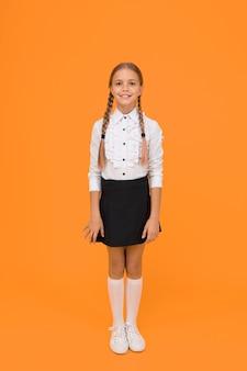 Witaj z powrotem w szkole. koncepcja ukończenia szkoły. wykształcenie podstawowe. idealna uczennica. mała uczennica z szczęśliwym uśmiechem. mała uczennica ładnie wygląda w szkolnym mundurku. śliczna uczennica z długimi włosami.