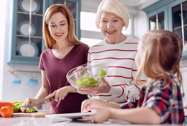 Witalna dziewczyna. troskliwa dziewczynka siedząca przy kuchennym blacie i podpowiadająca kolejne kroki w przygotowywaniu sałatek dla matki i babci podczas konsultacji z tabletem