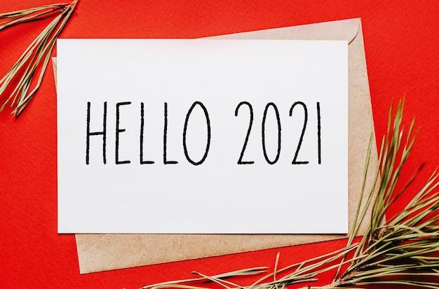Witam 2021 notatka świąteczna z gałęzi jodły na czerwonej odizolowanej powierzchni. koncepcja nowego roku