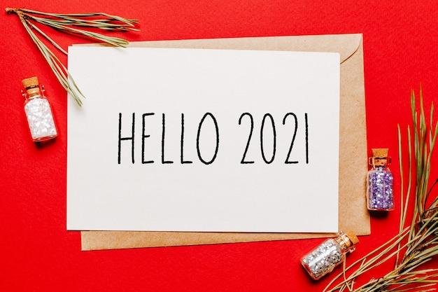 Witam 2021 notatka świąteczna z prezentem, gałąź jodły i zabawką na czerwonym tle na białym tle. koncepcja nowego roku