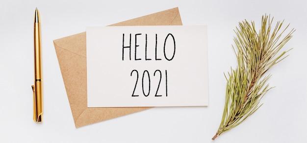 Witam 2021 notatka z kopertą, gałązką świerku i złotym piórem na białym tle