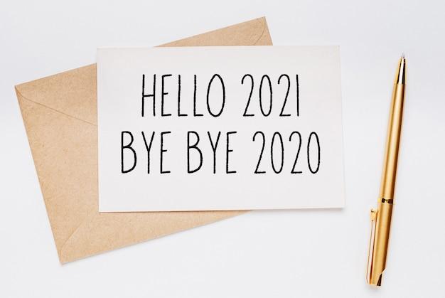 Witam 2021 pa pa pa 2020 notatka z kopertą i złotym długopisem na białym tle. wesołych świąt i nowego roku koncepcja