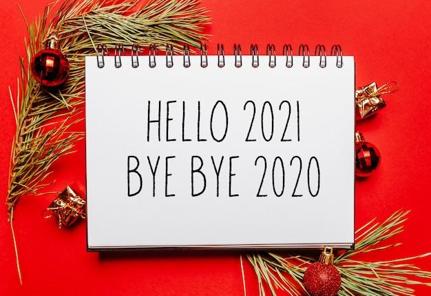 Witam 2021 pa pa pa 2020 świąteczna notatka z gałązką jodły i zabawką na czerwonej odizolowanej powierzchni. koncepcja nowego roku