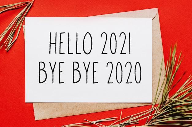 Witam 2021 pa pa pa 2020 świąteczna notatka z gałązką jodły na czerwonej izolowanej ścianie. koncepcja nowego roku