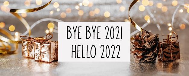 Witam 2022 pa pa 2021 notatka z kopertą, prezentami i złotą wstążką na białym tle