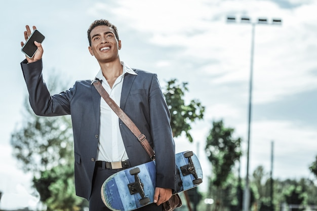 Witam cię. niski kąt radosny student płci męskiej, trzymając deskorolkę i machając ręką