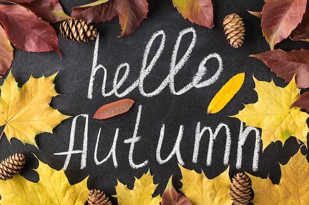 Witam jesień białą kredą napis na tablicy.