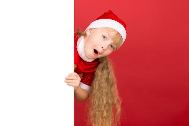 Witam. mała dziewczynka ubiera się w świąteczny strój, patrząc zszokowany zza dużego pustego plakatu z copyspace