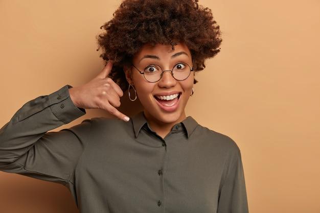 Witam, słyszę cię. zadowolona zachwycona kobieta naśladuje rozmowę telefoniczną, wykonuje ruchomy gest przy uchu, uśmiecha się radośnie, lubi komunikację na odległość, ubrana w ciemną koszulę, przezroczyste okulary.