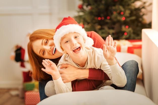 Witam. urocza rodzina nie może ukryć swoich emocji, relaksując się na sofie i żartując w bożonarodzeniowy poranek.