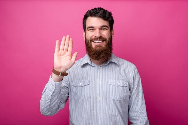 Witam, wesoły mężczyzna z brodą w swobodnym geście hi