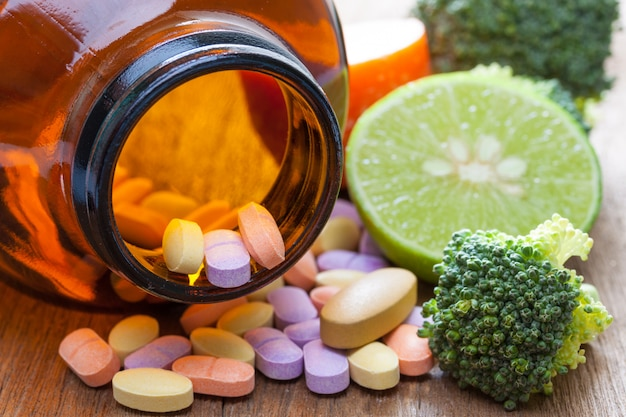 Witamina c pigułki, brokuły i cytryny na drewnianym stole, koncepcja opieki zdrowotnej i odnowy biologicznej