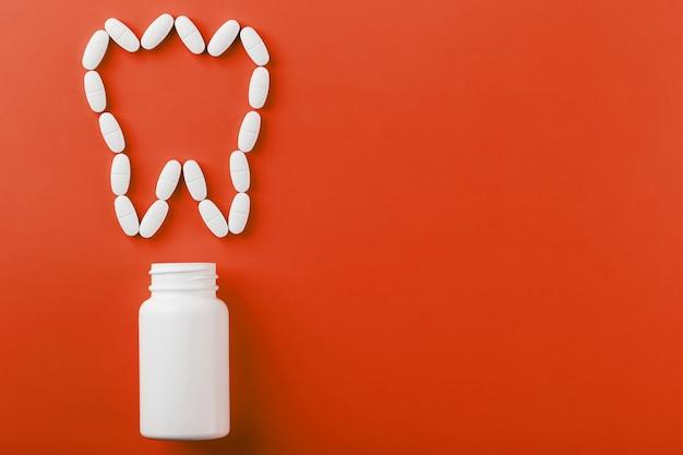 Witamina wapniowa w postaci zęba rozlana z białego słoika na czerwonym.