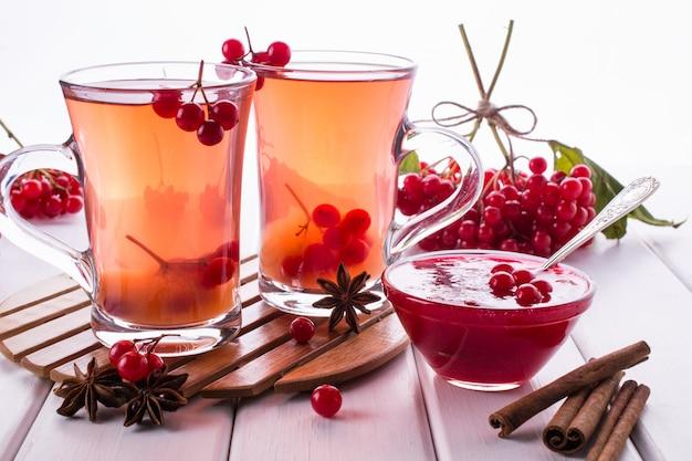 Witaminowy ciepły napój z kaliny jagodowej w szklanych filiżankach ze świeżymi, surowymi jagodami kaliny i paluszkami cynamonu, gwiazdki anyżu na białym stole w kuchni.