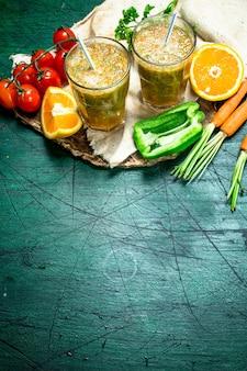 Witaminowy koktajl z pomidorami, słodką papryką, marchewką i pomarańczą. na tle rustykalnym.