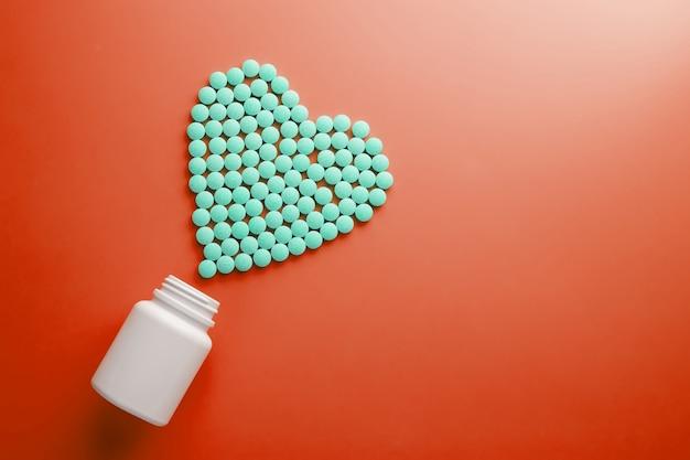 Witaminy b 12 na czerwonym podłożu w kształcie serca, wylane z białego słoika.