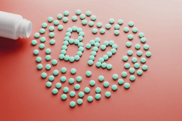 Witaminy b 12 w kształcie serca na czerwonym podłożu, wylane z białego słoika.