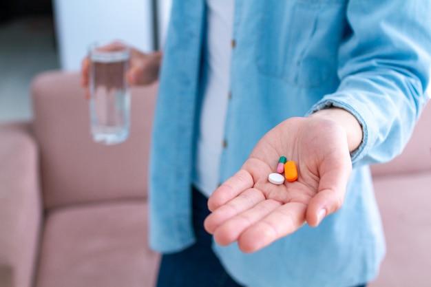 Witaminy i tabletki na dobre samopoczucie i leczenie chorób. medycyny kobieta bierze pigułki dla wellness