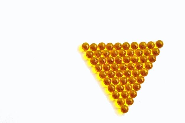 Witaminy przezroczyste żółte kulki ułożone w piramidę na białym tle.