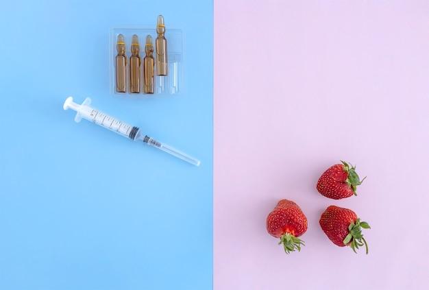 Witaminy w ampułkach strzykawki i truskawki