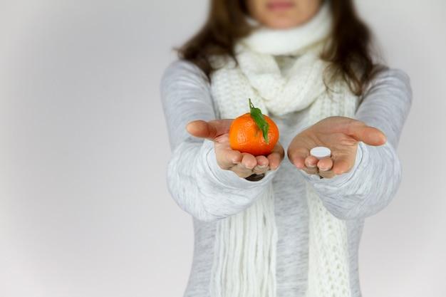 Witaminy z owoców lub narkotyków? chora młoda kobieta z szalikiem na szyi pokazuje mandarynkę w prawej dłoni i aspirynę w lewej