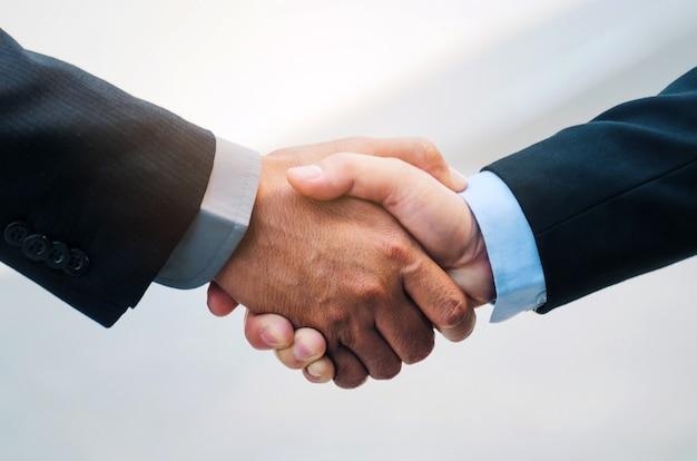 Witamy. sprawa. bliska biznes człowiek w uścisk dłoni garnitur po zakończeniu spotkania biznesowego