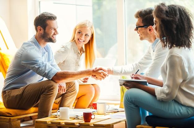 Witamy w naszym zespole! dwie szczęśliwe młode kobiety pracujące razem w strefie odpoczynku, podczas gdy dwóch mężczyzn ściska dłonie i uśmiecha się