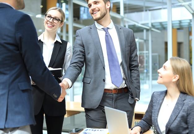 Witamy w naszym zespole. młodych nowoczesnych biznesmenów, ściskając ręce podczas pracy w kreatywnym biurze.