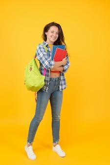 Witamy w szkole. ładna uczennica z powrotem do szkoły. szczęśliwa dziewczyna gotowa do szkoły żółte tło. 1 września. edukacja i wiedza. nauczanie prywatne. szkolenie. szkoła ma znaczenie.