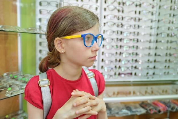 Witryna z okularami w sklepie optycznym, dziecko w okularach wybiera model okularów