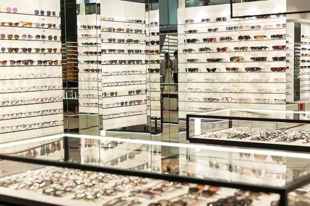 Witryny z różnymi okularami w dużym sklepie optycznym. moda i medycyna.