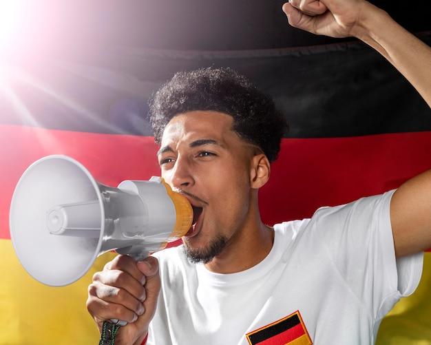 Wiwatujący mężczyzna mówiący przez megafon z niemiecką flagą