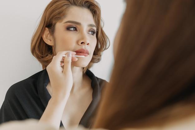 Wizażystka jest w pracy i nosi makijaż na swojej modelce