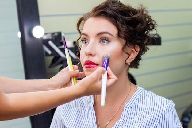 Wizażystka nakłada cienką warstwę matowego pudru za pomocą profesjonalnego pędzla do makijażu.