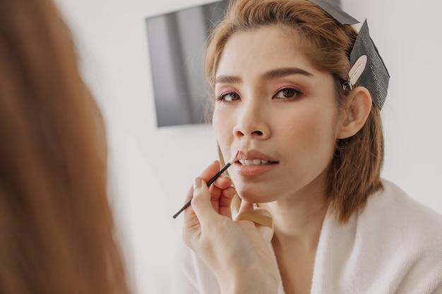 Wizażystka nakłada klientkom szminkę
