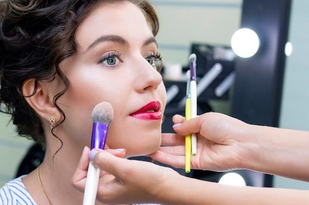 Wizażystka nakłada lekką warstwę matowego pudru za pomocą profesjonalnego pędzla do makijażu. dziewczyna u wizażysty