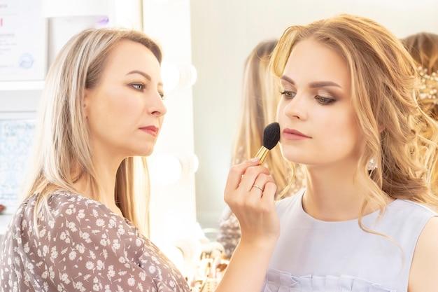 Wizażystka nakłada makijaż modelowy na twarz. makijaż ślubny, lekki makijaż wieczorowy, w odcieniach nude