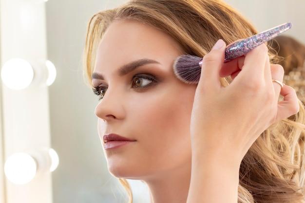 Wizażystka nakłada makijaż na modelkę. pędzel nakłada cienie, korektor. piękna dziewczyna model, portret. nude kolory w makijażu. makijaż ślubny, makijaż wieczorowy.
