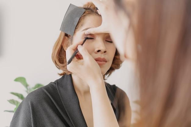 Wizażystka nakłada makijaż na oczy klienta