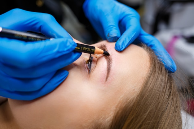Wizażystka nakłada ołówkiem do brwi szkic na brwi młodej dziewczyny. profesjonalny makijaż i pielęgnacja kosmetyczna skóry.