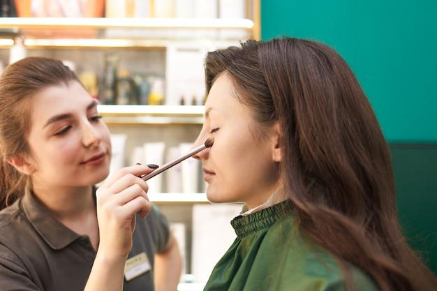 Wizażystka nakłada proszek na skórę klienta pędzlem do makijażu. proces makijażu w salonie kosmetycznym