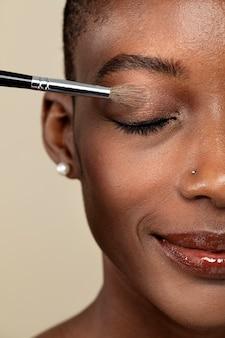 Wizażystka nakładająca cień do powiek na czarną kobietę