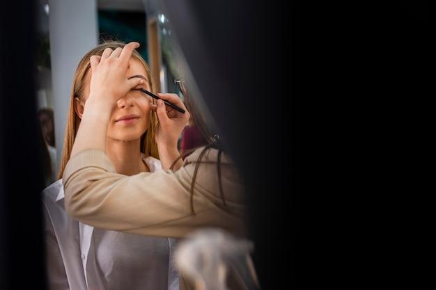 Wizażystka nakładająca cień do powiek pędzlem na twarz