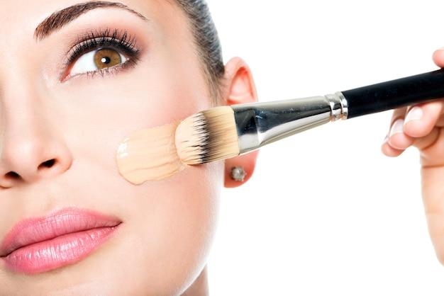 Wizażystka nakładająca płynny podkład tonalny na twarz kobiety