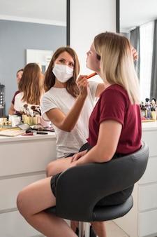 Wizażystka nosząca maskę medyczną od tyłu