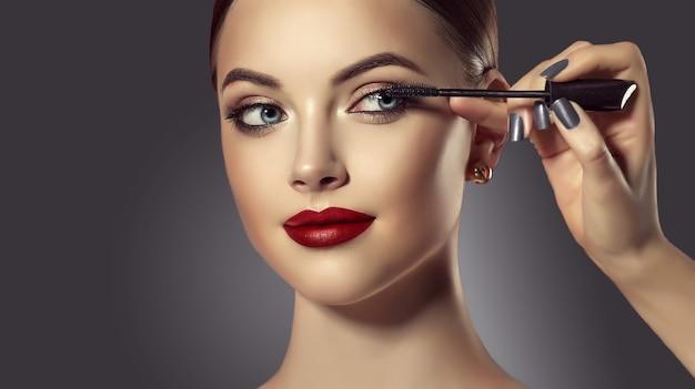Wizażystka pracuje nad twarzą idealnie wyglądającej młodej modelki. ręka mistrza makijażu farbuje rzęsy. kosmetyka, makijaż, manicure. portret uroda.