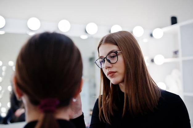 Wizażystka pracuje w salonie piękności. kobieta stosowania przez profesjonalnego makijażu mistrza.